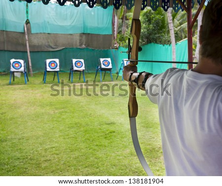Archer man pulls the bowstring and arrow, aiming at a target - stock photo