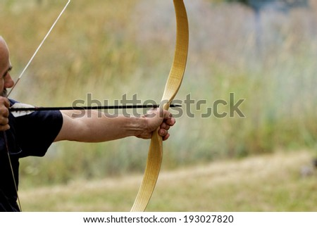 archery man shooting arrow with bow in the nature - stock photo