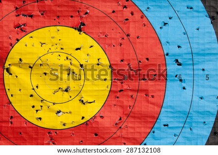Archery target close up with many arrow holes in gold red blue and black - stock photo