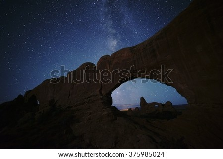 Arches National Park North Window, South Window, and Turret Arch under the Milky Way night sky in Autumn.   Stars are easy to see at night in the deserts of Utah near Moab. - stock photo