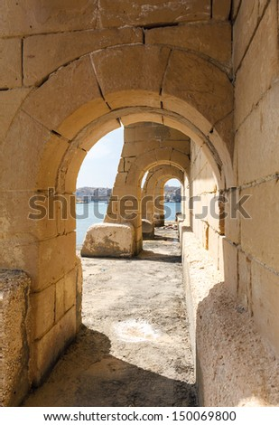 arches on seafront Kalkara overlooking the Grand harbor and Valletta - stock photo