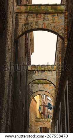 Arches over the narrow street in Venice. A game of light and shadow. - stock photo