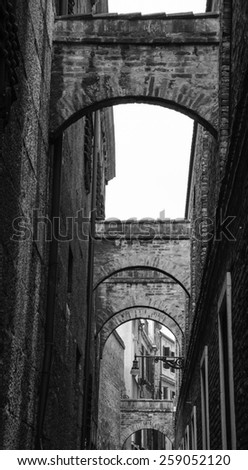 Arches over the narrow street in Venice.  A game of light and shadow. Aged photo. Black and white. - stock photo