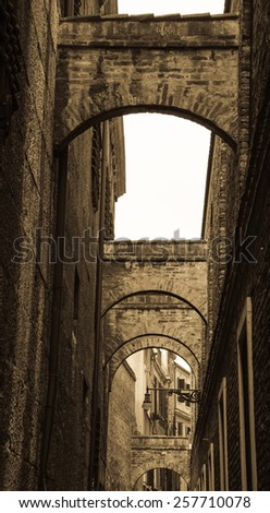 Arches over the narrow street in Venice.  A game of light and shadow. Aged photo. Sepia. - stock photo