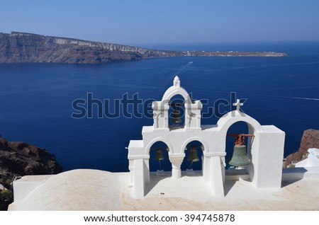 Arches with bells on the background of the caldera of Santorini - stock photo