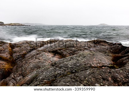 Archipelago in bad weather with waves roling in and crushes on cliffs on the shore - stock photo