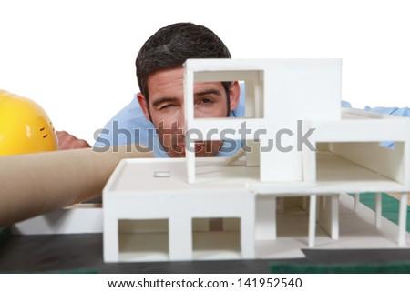 Architect analyzing scale model of building - stock photo
