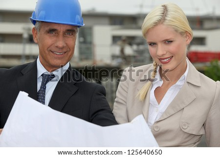 Architect and assistant working on-site - stock photo