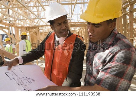 Architect and builder at construction site - stock photo