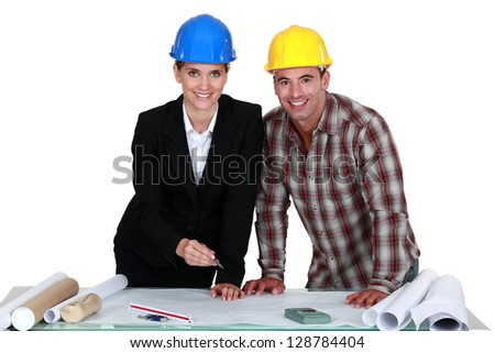 Architect and builder looking at plans - stock photo