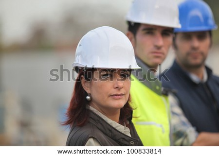 Architect and builders on site - stock photo