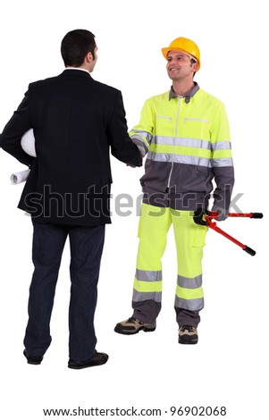 Architect and construction worker shaking hands - stock photo