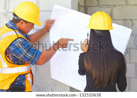 Architect and foreman reviewing blueprint together at construction site. - stock photo
