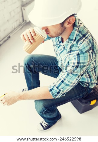 architect and home renovation concept - builder sitting on toolkit and drinking take away coffee - stock photo