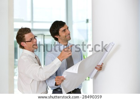 Architect and young designer holding blueprints - stock photo
