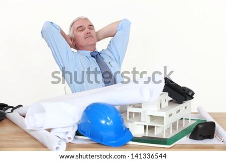 Architect asleep on the job - stock photo