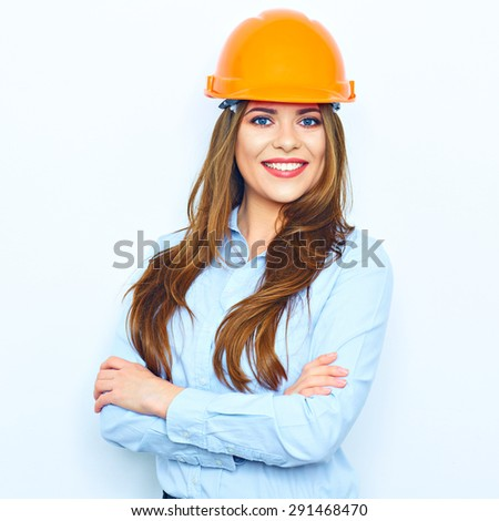 Architect business woman standing against white wall with crossed arms. Young smiling woman. Building helmet. - stock photo