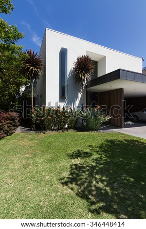 Architect design contemporary luxury double storey white rendered home with grass and carport - stock photo