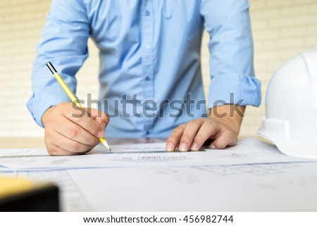 architect drawing architectural project on blueprint, engineering concept, soft focus, vintage tone