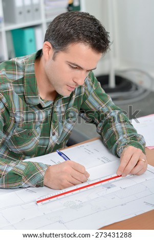 Architect drawing at his desk - stock photo
