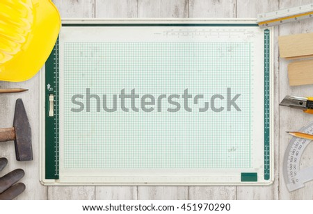 Architect drawing board surrounded by construction tools. - stock photo