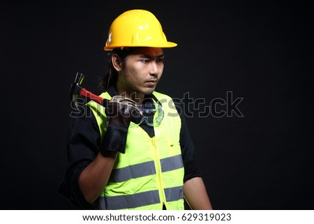 Architect Engineer in hard hat,  safety vest equipment, thick gloves, metal hammer and protector glasses goggle, studio lighting black background copy space