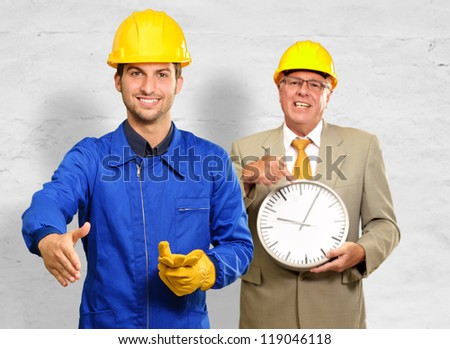 Architect Gesturing In Front Of Engineer Holding Clock, Indoors - stock photo