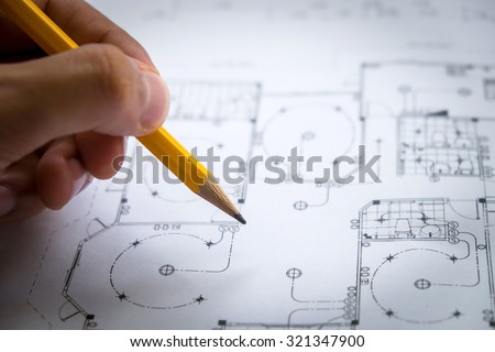 architect hand with pencil drawing blueprints - stock photo