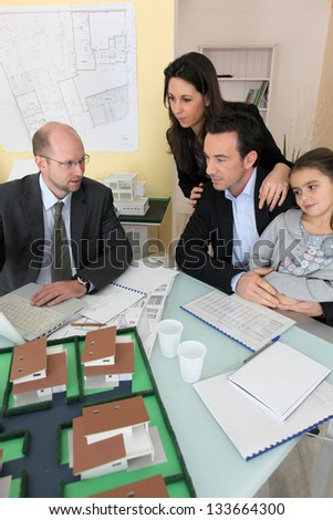 Architect having meeting with young family - stock photo