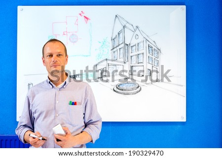 Architect, holding a white board marker, standing in front of a design sketch of a residential structure on the glass board behind him - stock photo