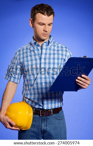 Architect holding hardhat and looking at clipboard - stock photo