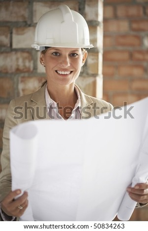 Architect holding plans at construction site - stock photo