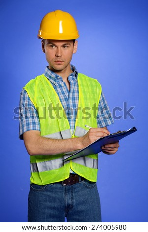Architect in coveralls and hardhat using clipboard - stock photo