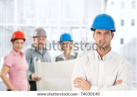 Architect in hardhat standing with team holding plan in office.? - stock photo
