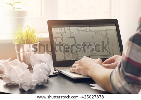 architect, interior designer working on laptop with floor plans - stock photo