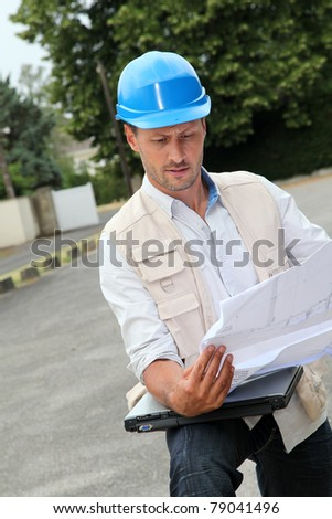 Architect looking at construction plan - stock photo