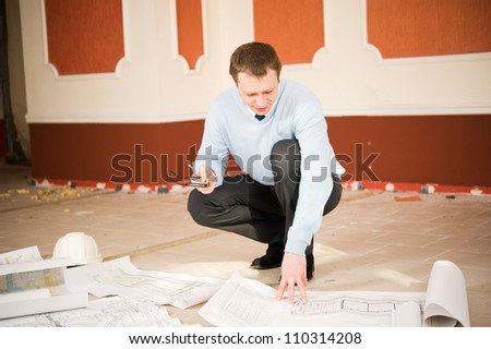 Architect looking blueprint on the floor. Reconstruction interior. - stock photo