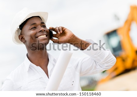 Architect making business call at a construction site  - stock photo