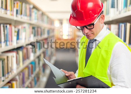 Architect man wearing a red helmet and reading from a black folder. Over library background - stock photo