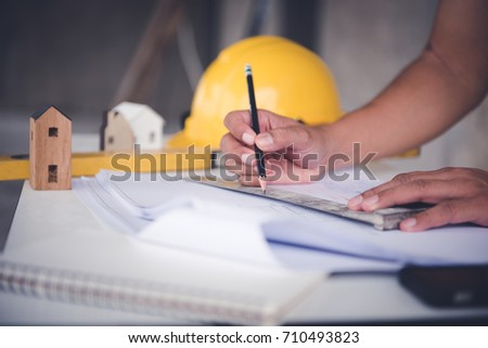 architect man working with blueprints,engineer inspection in workplace for architectural plan,sketching a construction project ,selective focus.