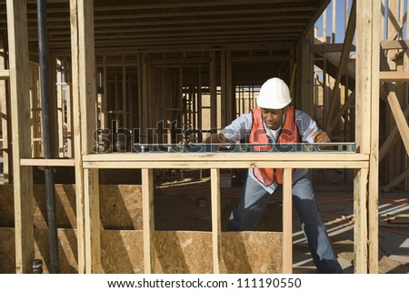 Architect measuring with bubble level at a construction site - stock photo