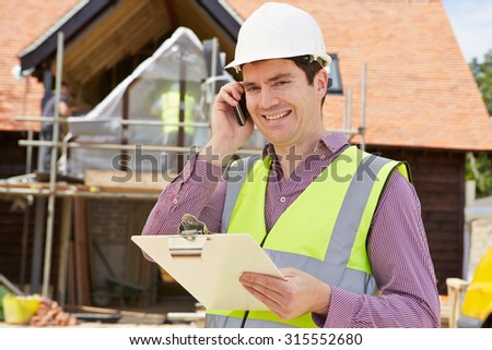 Architect On Building Site Using Mobile Phone - stock photo