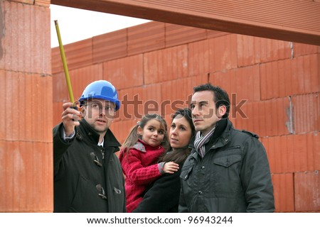 Architect on site with a young family - stock photo