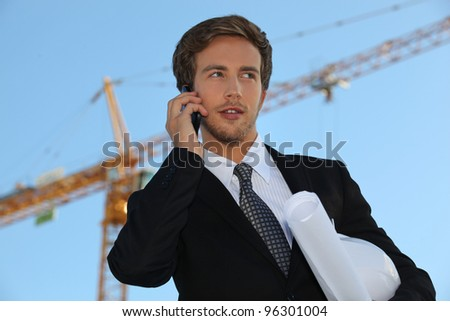 Architect on site with plans and cellphone - stock photo