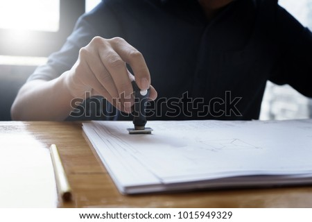 Architect engineer stamping document blueprint on stock photo architect or engineer stamping the document or blueprint on wooden desk architectural project construction malvernweather Gallery