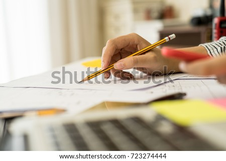 Architect or planner working on drawings for construction plans at a table