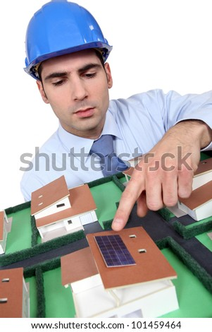 Architect pointing to solar panel on model house - stock photo