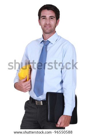 Architect posing with laptop under-arm - stock photo