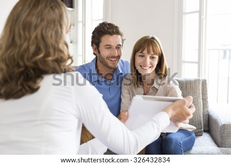 Architect presenting a new project  on digital tablet to a cheerful young couple - stock photo
