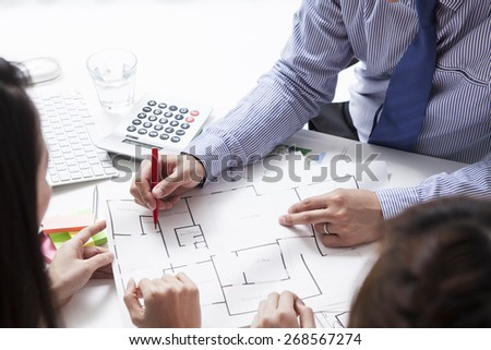 Architect presenting a new project to a smiling woman - stock photo